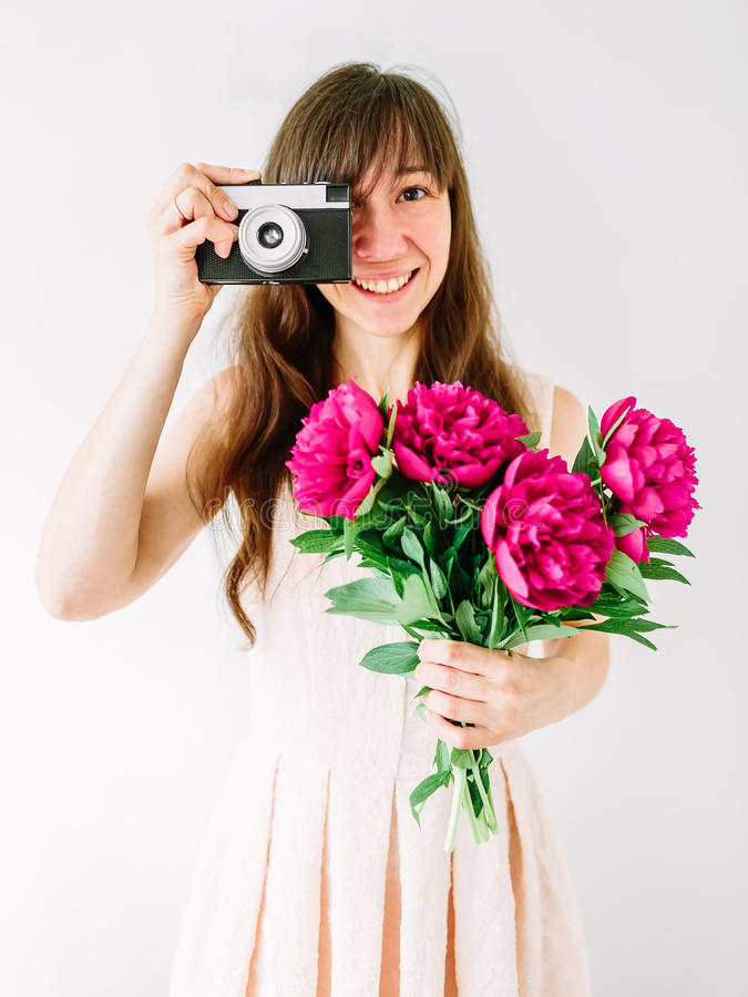 Gelukkige jonge vrouwenholding in het boeket van de handenpioen en oude uitstekende camera Zoet romantisch ogenblik Glimlachende  stock afbeeldingen