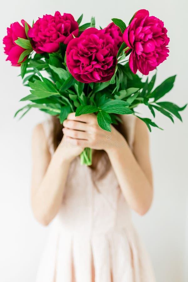 Gelukkige jonge vrouwenholding in het boeket van de handenpioen Vrouw in roze kleding Zoet romantisch ogenblik stock foto's