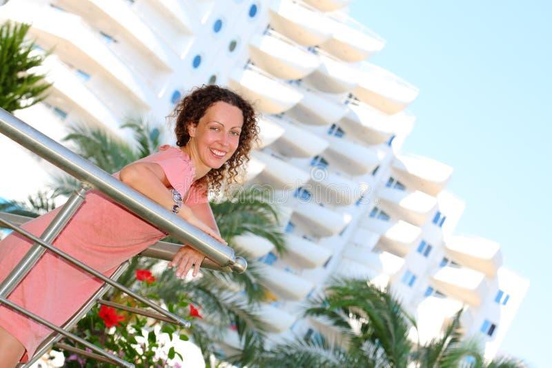Gelukkige jonge vrouwentribunes op balkon stock fotografie