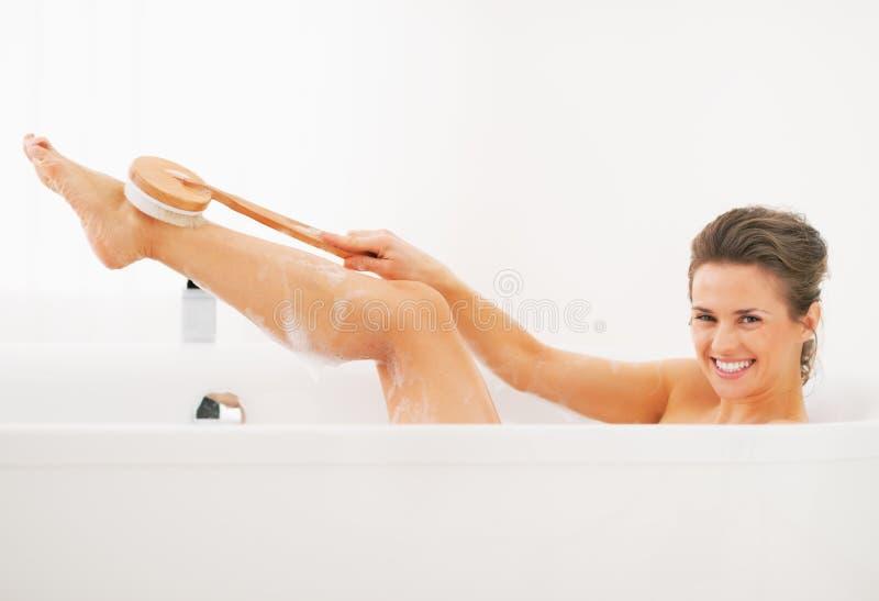 Gelukkige jonge vrouwenwas met lichaamsborstel in badkuip stock afbeelding