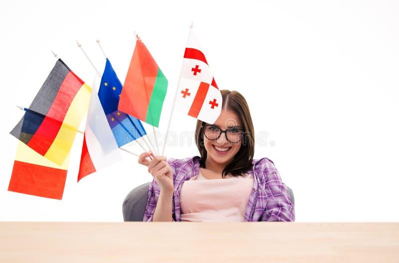 Gelukkige jonge vrouwenzitting bij de lijst met internationale vlaggen royalty-vrije stock fotografie