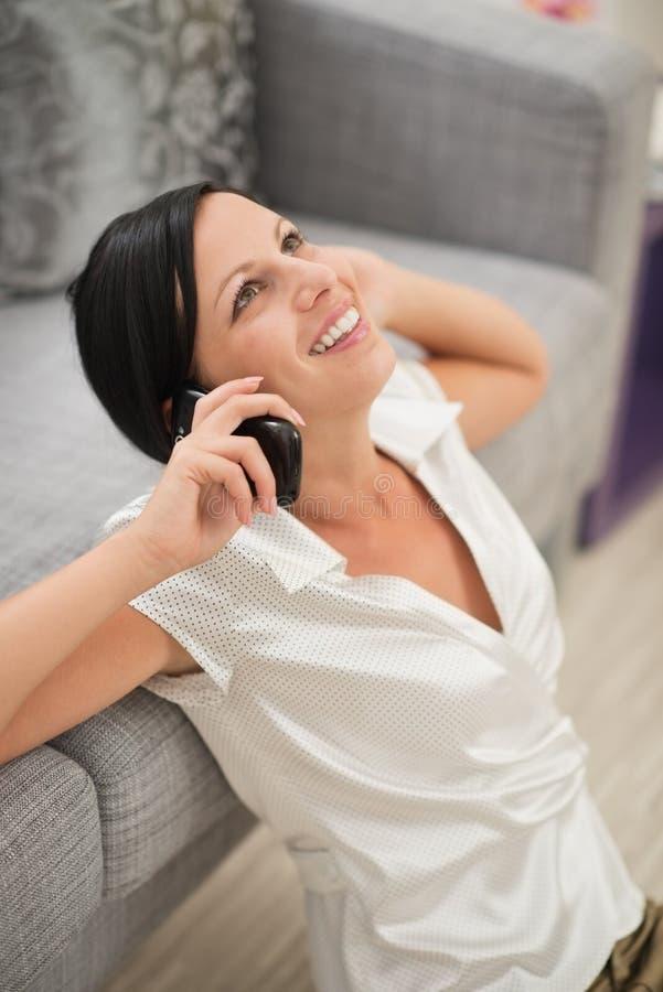 Gelukkige vrouwenzitting op vloer en mobiel spreken royalty-vrije stock afbeelding
