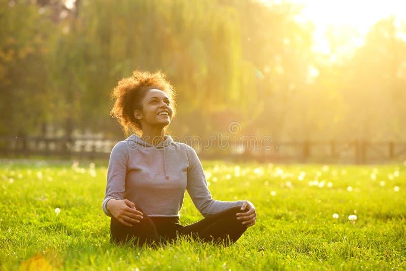 Gelukkige jonge vrouwenzitting in yogapositie royalty-vrije stock afbeeldingen