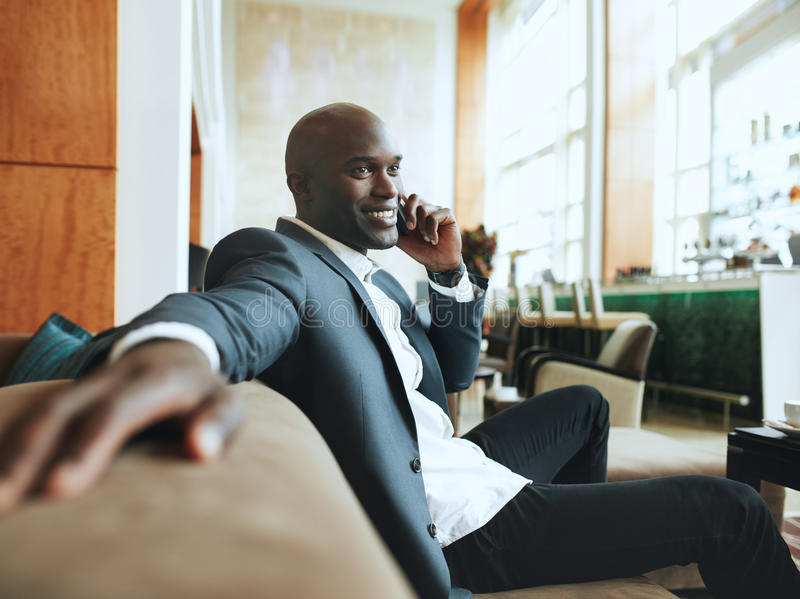 Gelukkige jonge zakenman die bij hotelhal wachten die telefoonca maken stock foto's