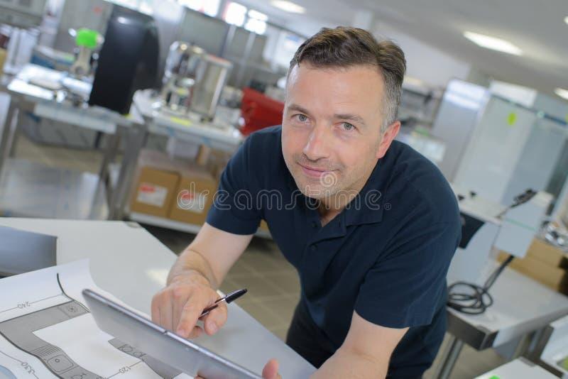 Gelukkige jonge zakenman die de digitale tablet van PC in bureau gebruiken royalty-vrije stock afbeeldingen