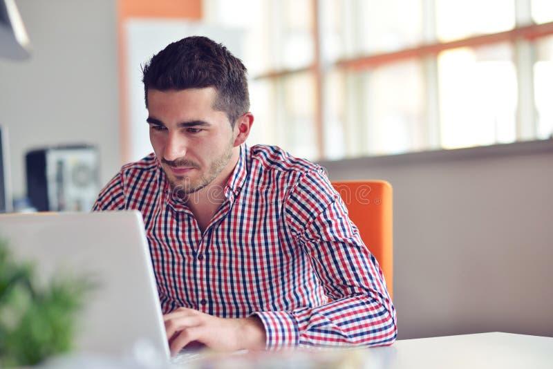 Gelukkige jonge zakenman die laptop met behulp van bij zijn bureau royalty-vrije stock afbeeldingen
