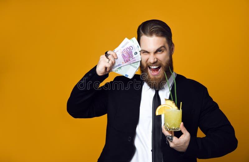 Gelukkige jonge zakenman die met glas van cocktail in formele kleding bos van geldbankbiljetten houden stock foto