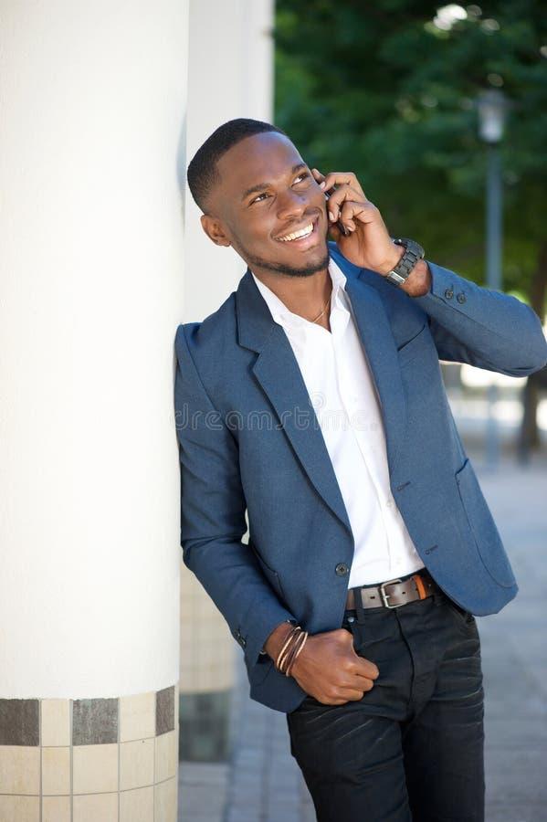 Gelukkige jonge zakenman die met mobiele telefoon roepen stock afbeelding
