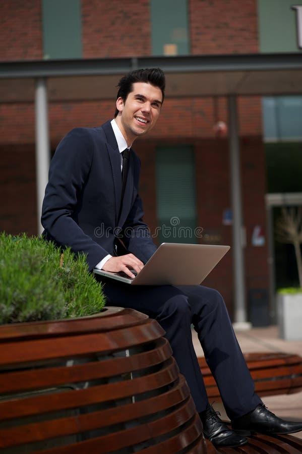 Gelukkige jonge zakenman die in openlucht met laptop werken royalty-vrije stock afbeeldingen