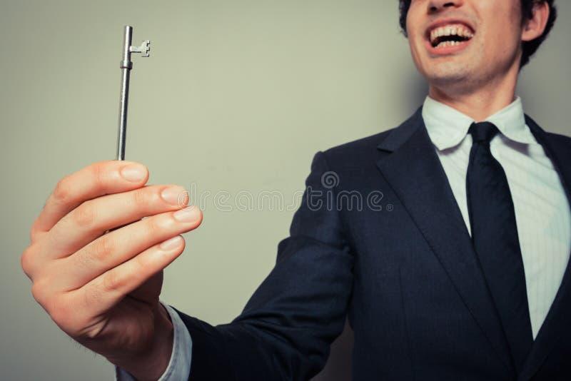 Gelukkige jonge zakenman met sleutel stock afbeelding