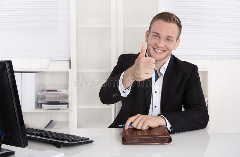 Gelukkige jonge zakenmanzitting die in zijn bureau duim op Duitsland maken royalty-vrije stock afbeeldingen