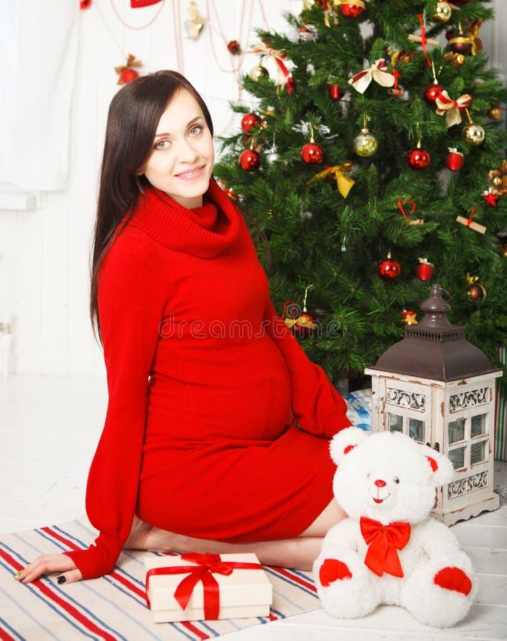Gelukkige jonge zwangere vrouw dichtbij de Kerstboom stock afbeelding
