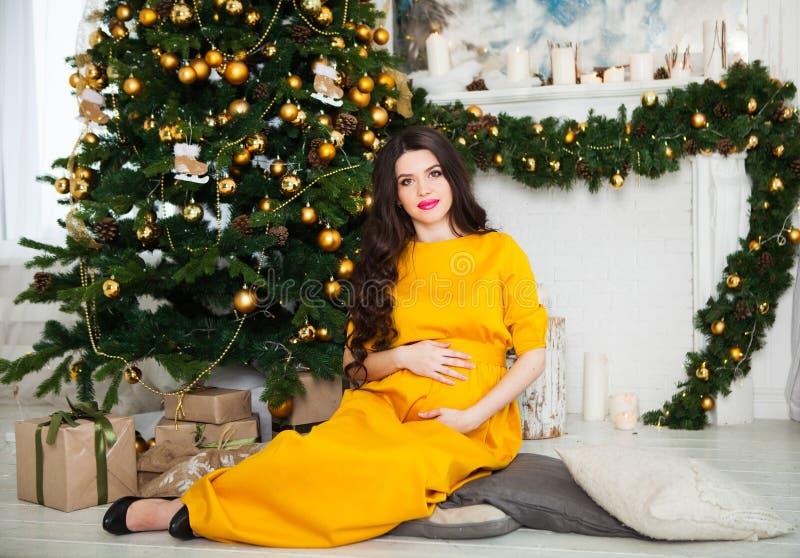 Gelukkige jonge zwangere vrouw in gele kledingszitting dichtbij Chri stock afbeelding