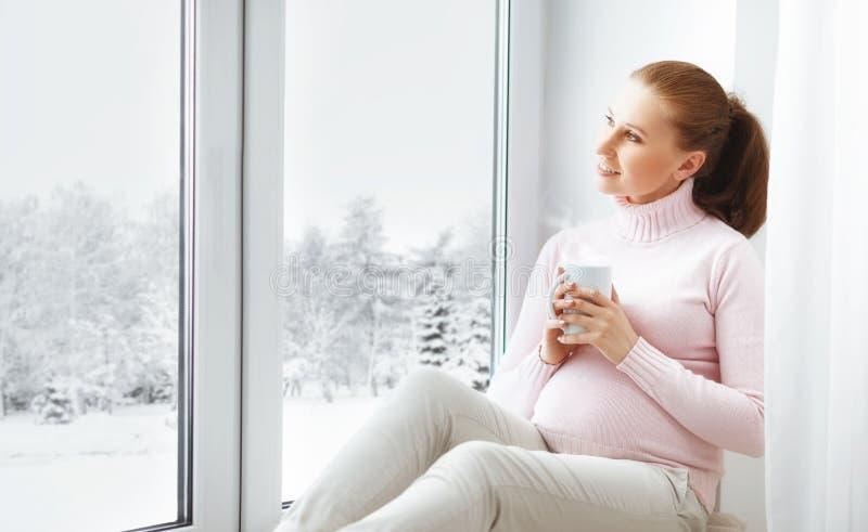 Gelukkige jonge zwangere vrouw met kop thee op venster royalty-vrije stock afbeelding