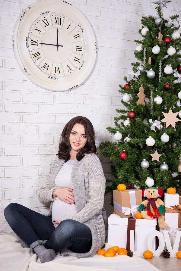 Gelukkige jonge zwangere vrouwenzitting met Kerstmisboom royalty-vrije stock foto's