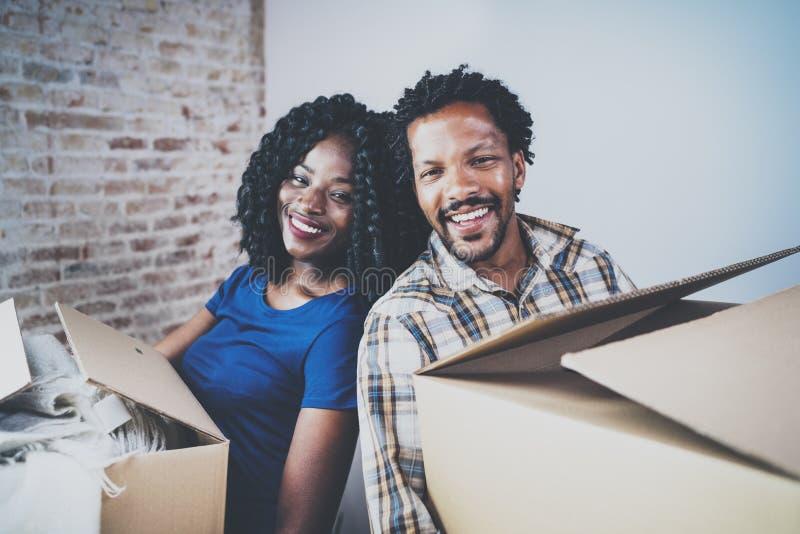 Gelukkige jonge zwarte Afrikaanse paar bewegende dozen in nieuw huis samen en makend het succesvol leven Vrolijke familie stock fotografie