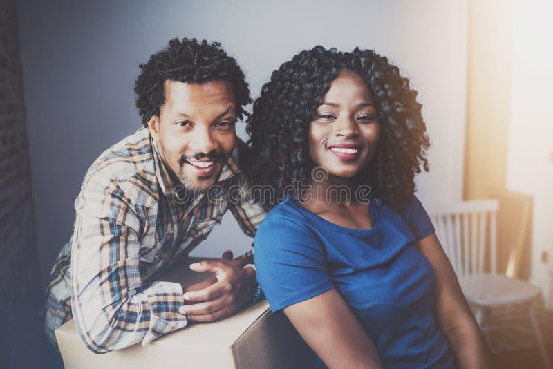 Gelukkige jonge zwarte Afrikaanse paar bewegende dozen in nieuwe flat samen en makend het mooi leven Vrolijke familie stock foto