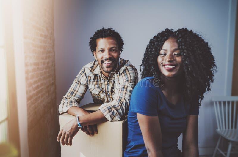 Gelukkige jonge zwarte Afrikaanse paar bewegende dozen in nieuwe flat samen en makend het succesvol leven Vrolijke familie stock foto's