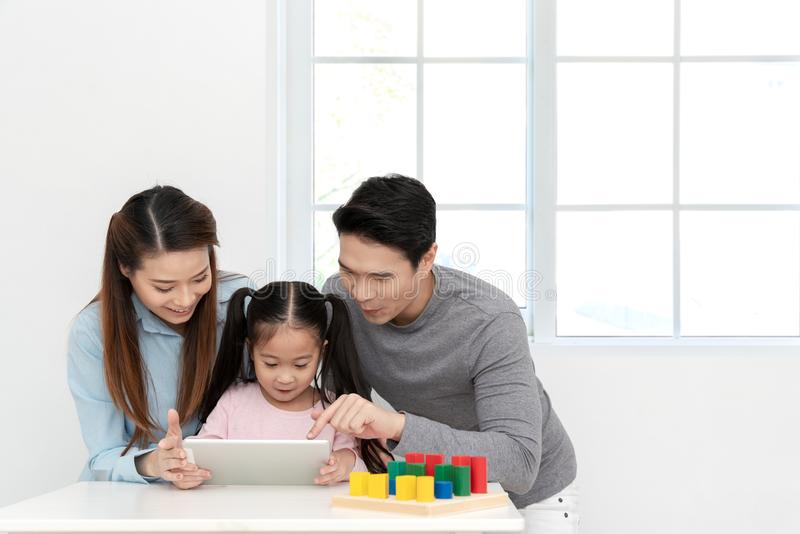 Gelukkige jongelui weinig Aziatisch leuk meisje die of op digitale tablet, laptop letten spelen of mobiel met vrolijke ouders op  stock afbeelding