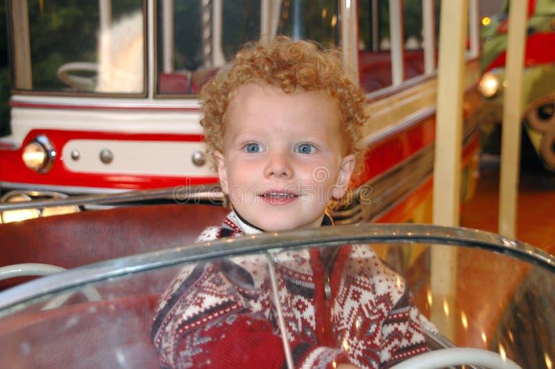 Gelukkige jongen in carrousel stock foto's