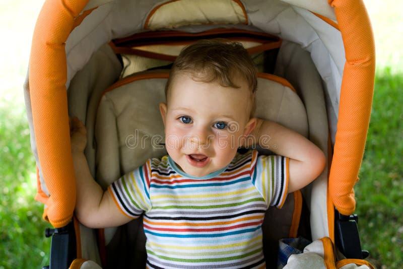 Gelukkige jongen in de kinderwagen stock afbeelding