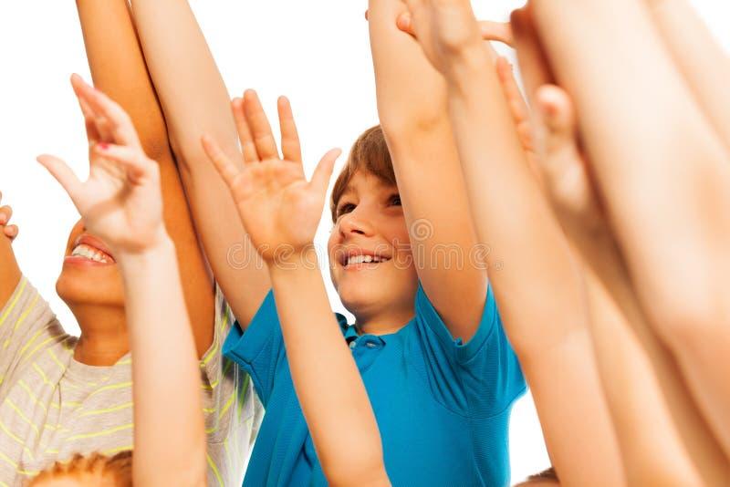 Gelukkige jongen in de menigte met opgeheven handen stock fotografie