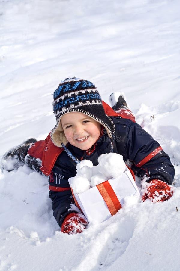 Gelukkige jongen in de sneeuw met sneeuwballen in een doos stock fotografie