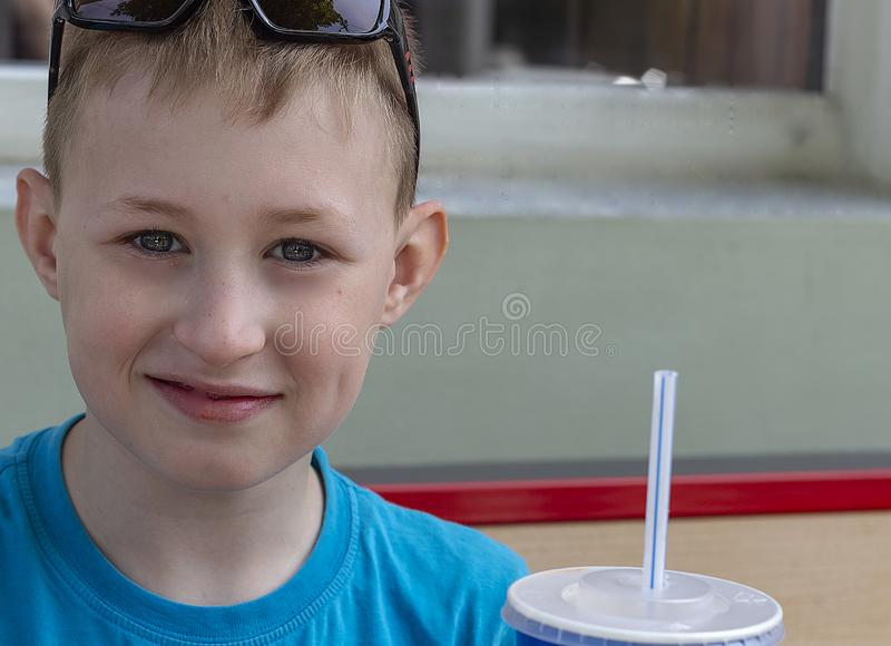 Gelukkige jongen in de stadskoffie op de straat stock afbeelding