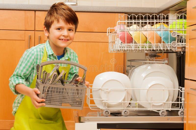 Gelukkige jongen die bestek van de afwasmachine terugtrekken stock foto's