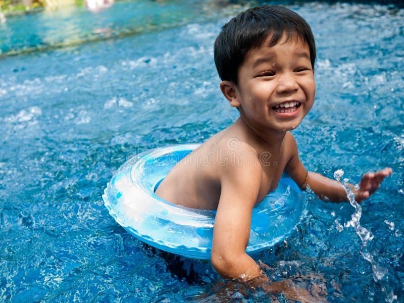 Gelukkige jongen die in de pool zwemt stock afbeelding