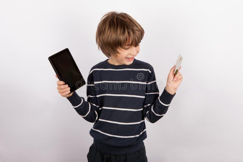 Gelukkige jongen die een apparaat van tabletpc en een betaalpas houden royalty-vrije stock afbeeldingen