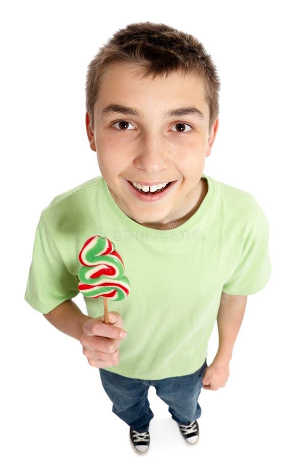 Gelukkige jongen die een lollysuikergoed houdt stock afbeelding