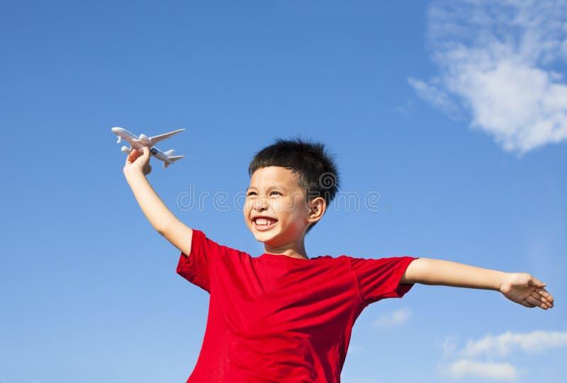 Gelukkige jongen die een vliegtuigstuk speelgoed met blauwe hemel houden stock fotografie