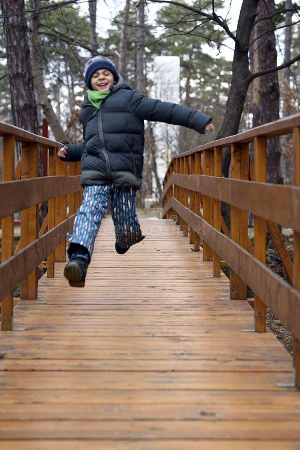 Gelukkige jongen die en op een houten brug in het bos springen lopen royalty-vrije stock afbeeldingen