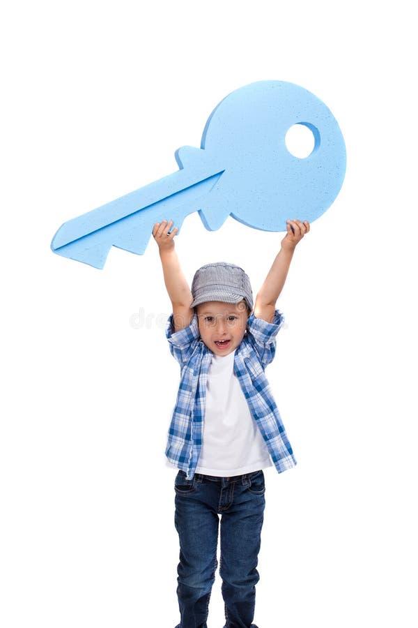 Gelukkige jongen die grote blauwe sleutel houden Nieuw huisconcept Ge?soleerd op wit royalty-vrije stock afbeeldingen