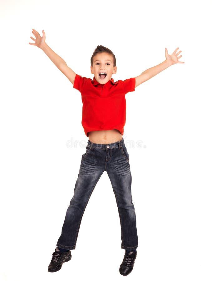 Gelukkige jongen die met opgeheven omhoog handen springt royalty-vrije stock foto's