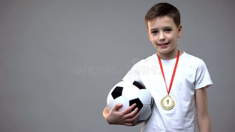 Gelukkige jongen die met winnaarmedaille glimlachen op borst, die voetbalbal, kampioen houden royalty-vrije stock foto