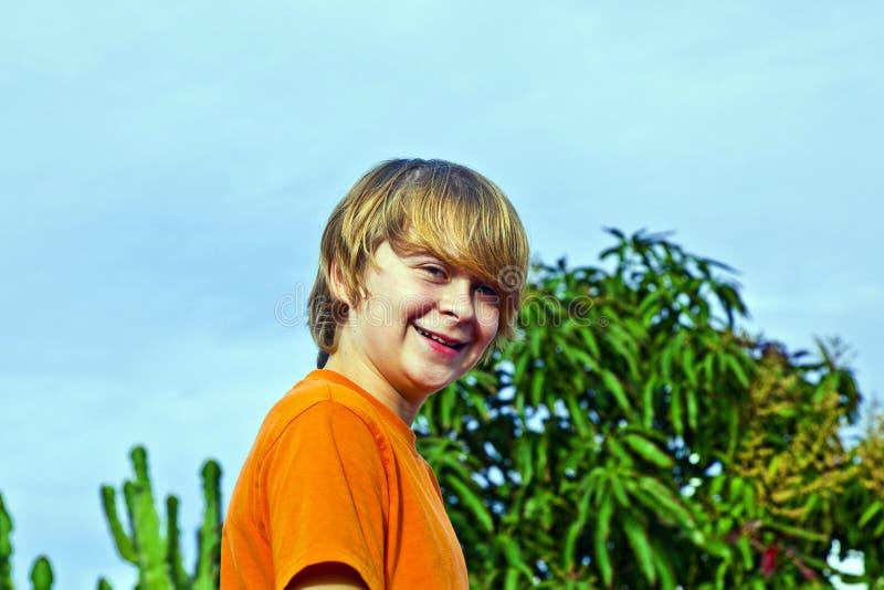Gelukkige jongen die onder blauwe hemel glimlachen royalty-vrije stock afbeeldingen