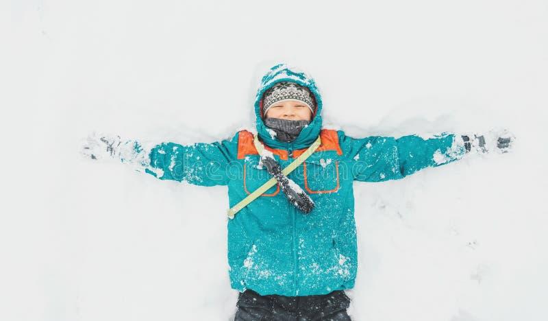 Gelukkige jongen die op sneeuw liggen stock afbeelding