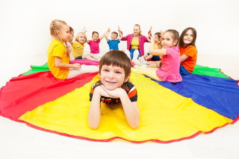 Gelukkige jongen die op valscherm tijdens sociale spelen leggen stock afbeeldingen
