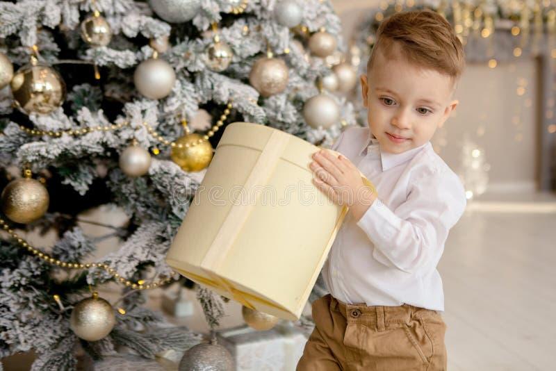 Gelukkige jongen die op vloer met Kerstmisgiften leggen in verfraaide ruimte royalty-vrije stock foto