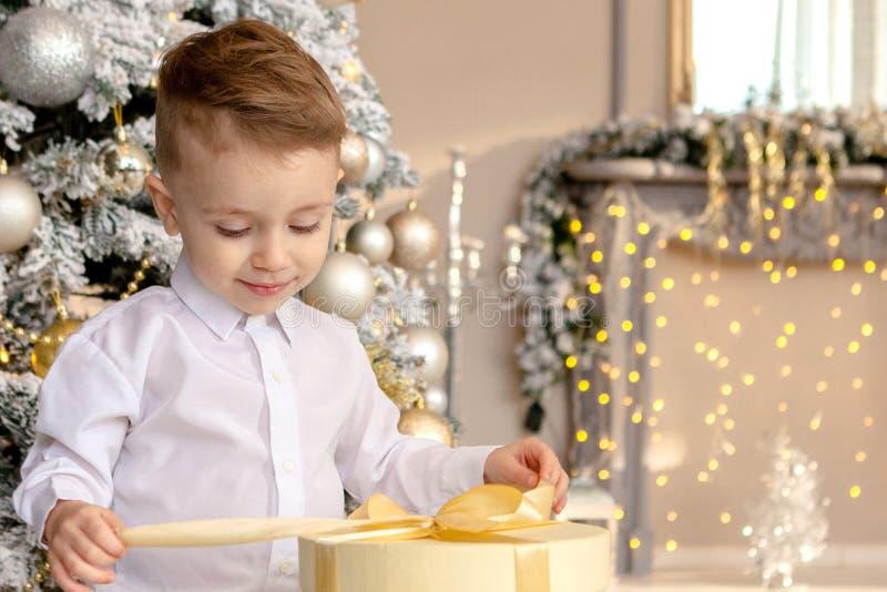 Gelukkige jongen die op vloer met Kerstmisgiften leggen in verfraaide ruimte stock foto