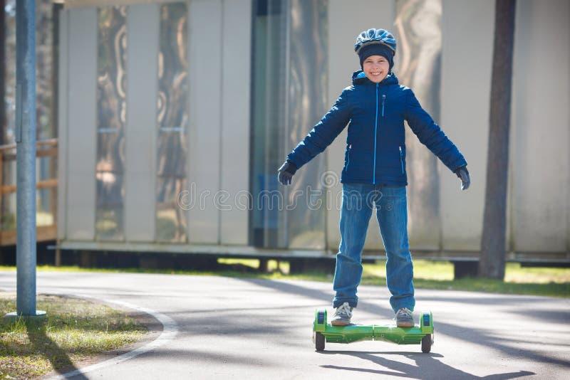 Gelukkige jongen die op zelf-in evenwicht brengt dek in stadspark berijdt stock fotografie
