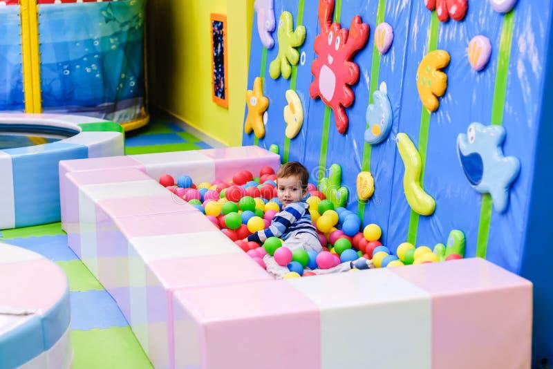 Gelukkige jongen die pret in balkuil hebben in jonge geitjespretpark en binnenspelcentrum Kind het spelen met kleurrijke ballen i stock foto's