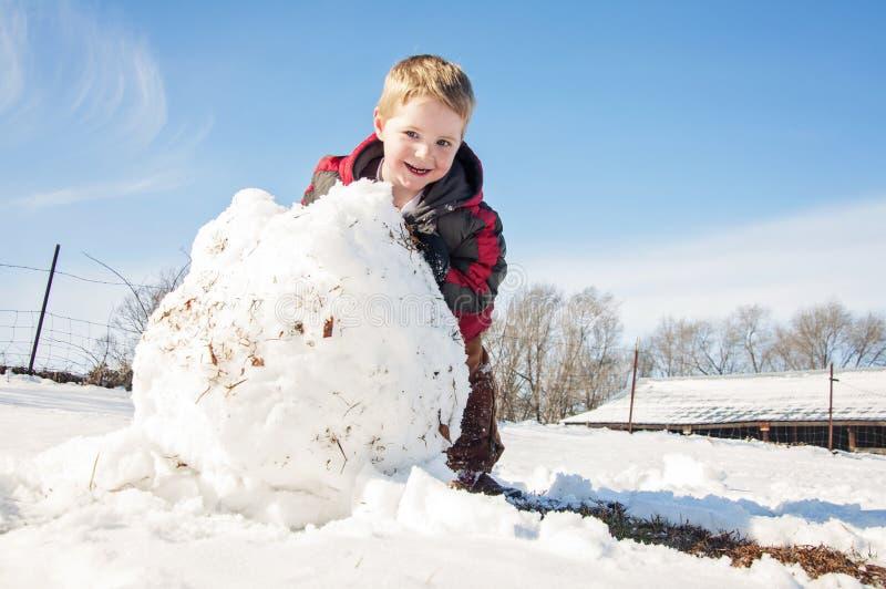 Gelukkige jongen die reusachtige sneeuwbal rollen royalty-vrije stock foto