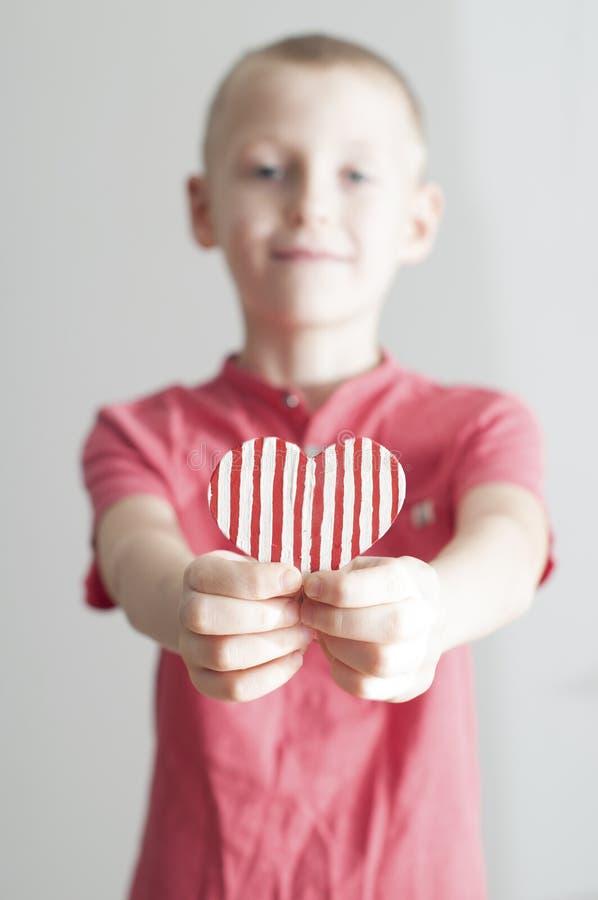 Gelukkige jongen die rode gestripte hartvorm geven stock foto