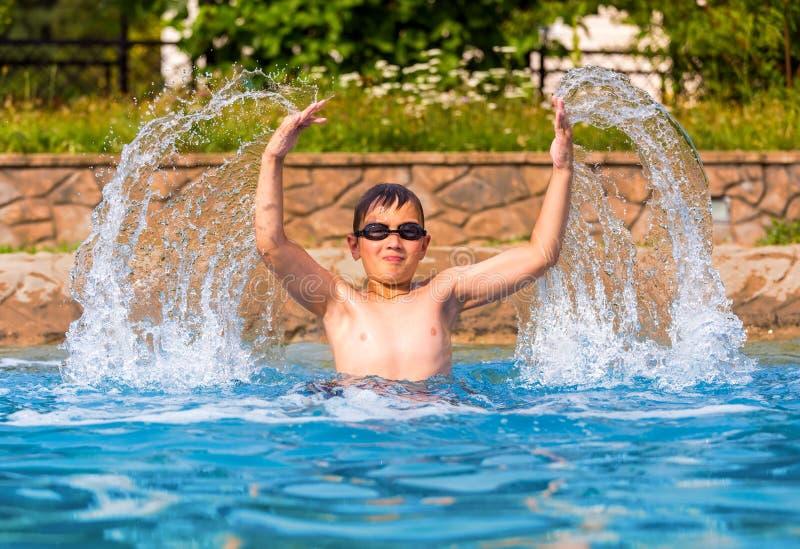 Gelukkige jongen in een zwembad stock foto