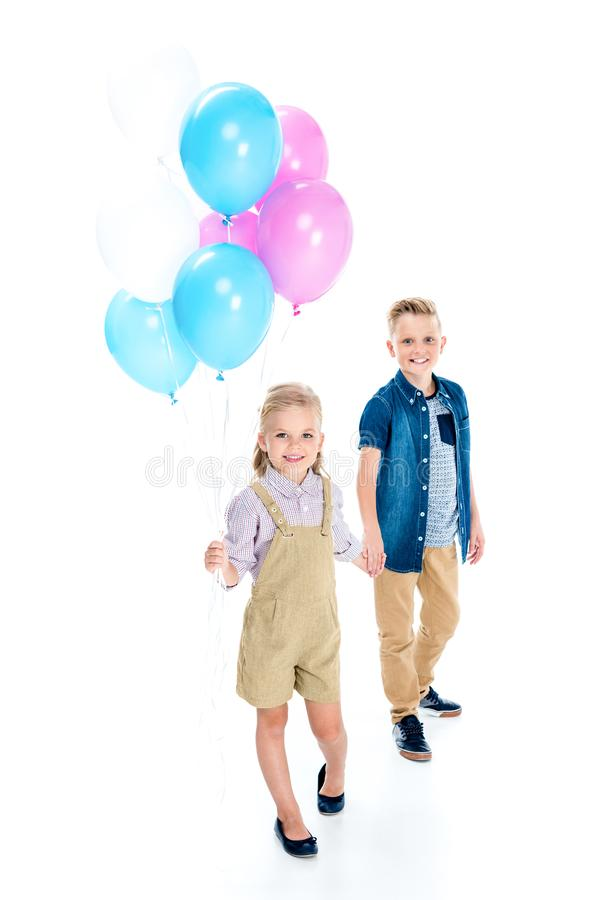 gelukkige jongen en leuk meisje met ballons die zich en handen verenigen houden royalty-vrije stock afbeeldingen