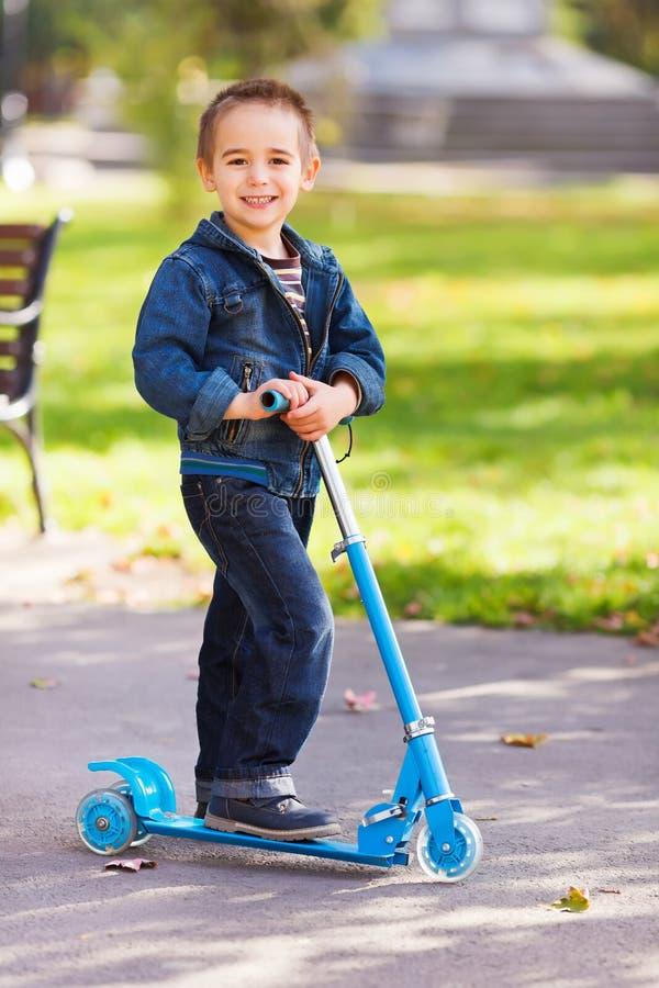 Gelukkige jongen met autoped in speelplaats stock afbeeldingen