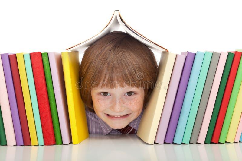 Gelukkige jongen met kleurrijke boeken stock fotografie